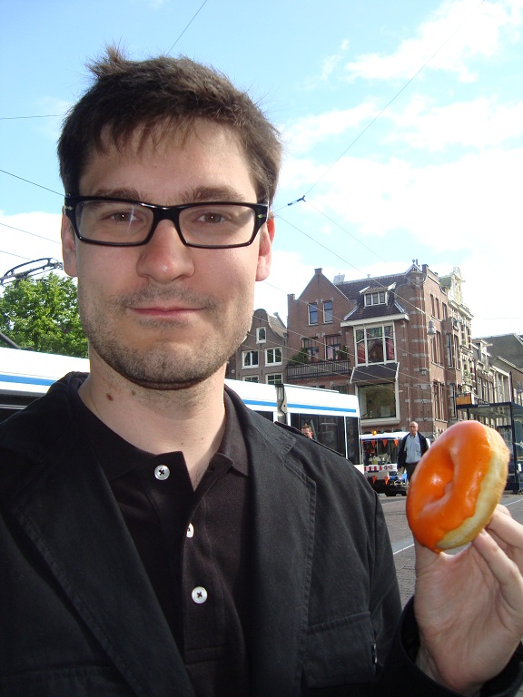 That's me in Amsterdam, half-awake and really happy to have an orange doughnut for breakfast